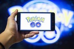 De hand die een cellphone houden die Pokemon spelen gaat spel met onduidelijk beeldachtergrond stock foto