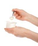 De hand die een lepel met yoghurt houden Stock Afbeeldingen