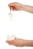 De hand die een lepel met yoghurt houden Stock Afbeelding