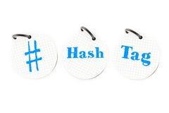 De hand die # hashtag verwoordt op cirkeldocument notastootkussen op witte bedelaars schrijven Stock Foto