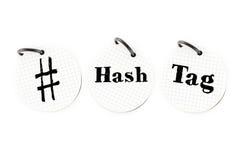 De hand die # hashtag verwoordt op cirkeldocument notastootkussen op witte bedelaars schrijven Royalty-vrije Stock Afbeeldingen