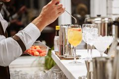 De hand die van de barman een cocktail dienen Oranje cocktails met fruitplakken op de barteller stock afbeeldingen