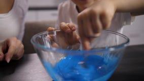 De hand die van de close-upjongen blauwe massa voor slijm mengen stock footage