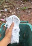 De hand die van de close-upmens leeg plastic glas water werpt in een groene bak voor de concepten milieubesparing royalty-vrije stock foto