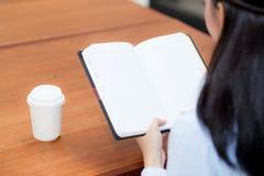 De hand die van de close-upvrouw op notitieboekje op houten lijst, het meisjeswerk met document bij koffiewinkel schrijven Stock Foto's