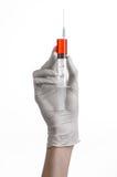 De hand die van de arts een spuit, witte gloved hand, een grote spuit houden, de arts maakt een injectie, witte achtergrond Stock Fotografie
