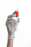 De hand die van de arts een spuit, witte gloved hand, een grote spuit houden, de arts maakt een injectie, witte achtergrond Royalty-vrije Stock Afbeelding