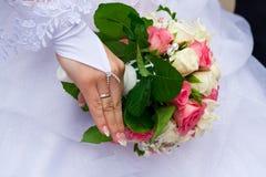 De hand die van de bruid het boeket houdt stock afbeelding