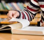 De hand die van de close-upmens pagina van boek gaan wegknippen Royalty-vrije Stock Foto