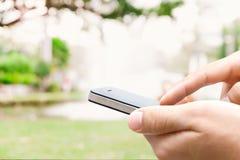 De hand die van de close-upmens slimme telefoon met behulp van Stock Afbeeldingen