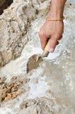 De hand die van de close-upmetselaar verse concrete mengeling met troffel uitspreiden Royalty-vrije Stock Afbeeldingen