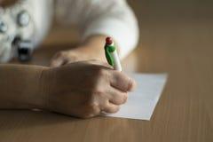De hand die van de close-upvrouw ` s op papier schrijven Stock Foto's
