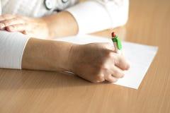 De hand die van de close-upvrouw ` s op papier schrijven Stock Fotografie