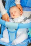 De hand die van de moeder het hoofdmeisje van de slaapbaby strijkt Stock Foto