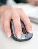 De hand die van de onderneemster een computermuis houdt Stock Foto's