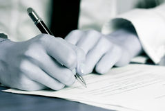 De hand die van de persoon een document ondertekenen Stock Afbeelding