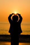 De hand die van de silhouetjongen een hartvorm maken Stock Foto's