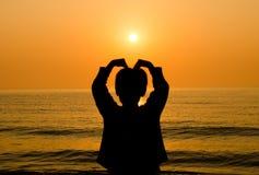 De hand die van de silhouetjongen een hartvorm maken Royalty-vrije Stock Afbeelding