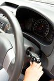 De hand die van de vrouw de motor van een auto begint Royalty-vrije Stock Foto's