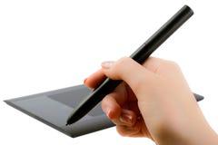 De hand die van de vrouw een pen houden om op de tablet te trekken stock foto's