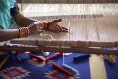 De hand die van de vrouw een tapijt in India weeft stock afbeeldingen