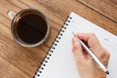 De hand die van de vrouw een zilveren pen op leeg notitieboekje houden Stock Foto