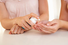 De hand die van de vrouw handdesinfecterend middel toepast Royalty-vrije Stock Afbeeldingen
