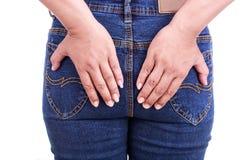 De hand die van de vrouw het achtereind houden: Conceptenhemorroïden stock afbeelding