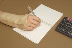 De hand die van de vrouw met handworteltunnelsyndroom berekeningen doen Stock Foto