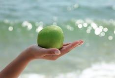 De hand die van de vrouw `s een groene appel houdt Stock Afbeeldingen