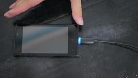 De hand die van de vrouw zwarte bliksem het laden kabel stoppen in smartphone stock video