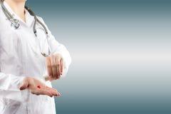 De hand die van de vrouwelijke arts pillen geven Sluit omhoog geschoten op vaag grijs Stock Foto