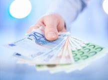 De hand die van de zakenman uit euro bankbiljetten bereiken Royalty-vrije Stock Foto's