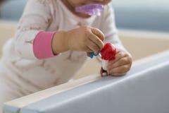 De hand die van een baby een stuk speelgoed houden stock foto