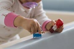 De hand die van een baby een stuk speelgoed houden stock foto's