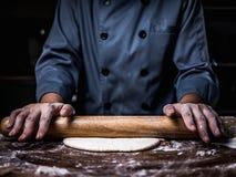 De hand die van de gebakjechef-kok Ruw Deeg met het bestrooien van witte bloem kneden stock foto