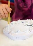 De Hand die van het Aziatische Meisje de Witte Kleur schilderen aan het Stuk van Papermache. royalty-vrije stock foto