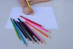 De hand die van het kind op een wit blad van document met kleurpotloden voorbereidingen treffen te schrijven Onderwijs en het con stock foto