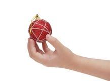 De hand die van het kind rode Kerstmisbal houdt Stock Foto
