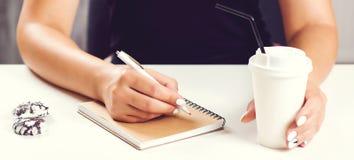 De hand die van het meisje die in blocnote schrijven op witte oppervlakte met koffiekop wordt geplaatst Spot omhoog Vrouw die not stock foto