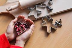De hand die van het meisje traditionele feestelijke koekjes maken Het bakken met liefdeconcept Moederdag, de Dag van Vrouwen, de  royalty-vrije stock afbeelding