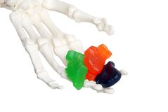De hand die van het skelet suikergoed aanbiedt Stock Afbeeldingen