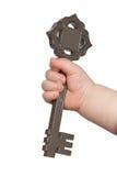 De hand die van kinderen een sleutel houdt Stock Afbeeldingen