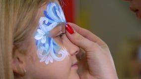 De hand die van de kunstenaar bergkristallen op het gezicht van het jonge geitje lijmen Close-upmotie stock footage