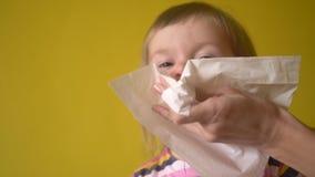 De hand die van de moeder meisje helpen om neus door servet te blazen stock footage