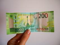 De hand die van de vrouw een nieuw Russisch bankbiljet van twee honderd roebels houden royalty-vrije stock afbeelding
