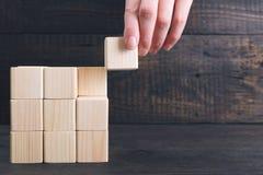 De hand die van de vrouw het definitieve stuk van houten kubus zet in plaats - voltooiingsconcept Beëindig het projectconcept royalty-vrije stock afbeelding