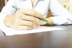 De hand die van de vrouw iets op papier dicht uitwerken Onherkenbare bedrijfsvrouw die in wit overhemd met een potlood schrijven royalty-vrije stock foto's