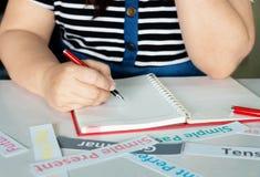 De hand die van de vrouw met gespannen kaarten schrijven royalty-vrije stock afbeeldingen
