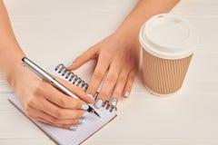 De hand die van de vrouw op notitieboekje schrijft Stock Foto